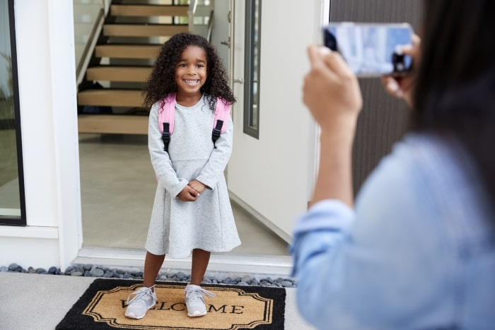 Little girl smiling at front door on first day of school.