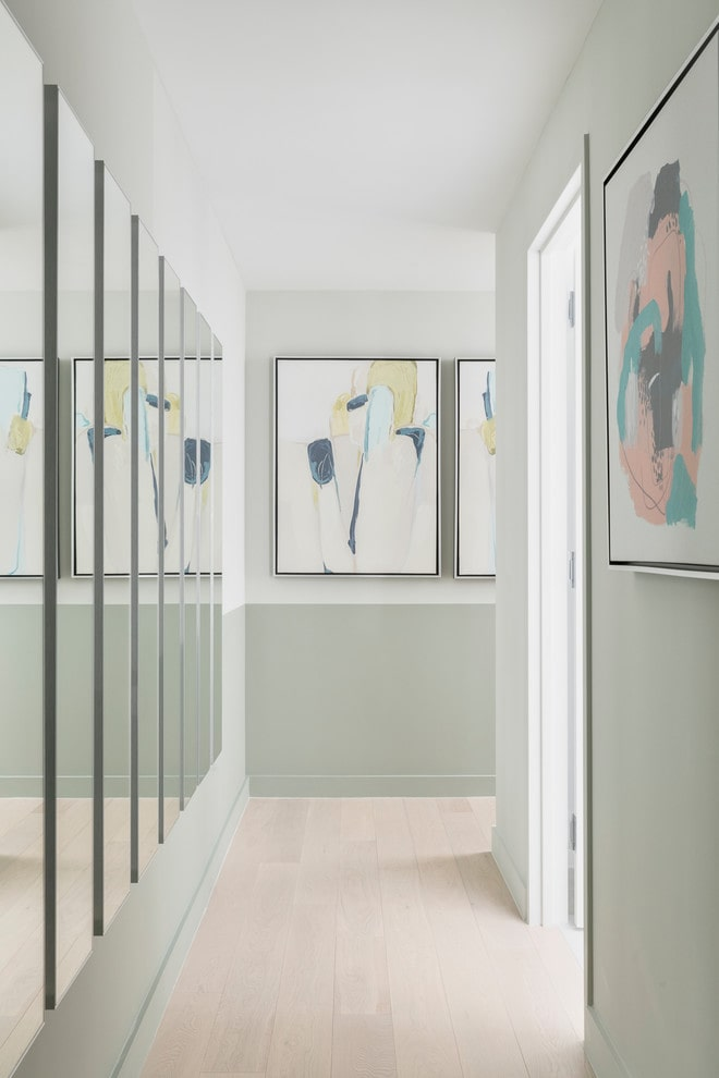 Narrow hallway with mirrors and mid century artwork.