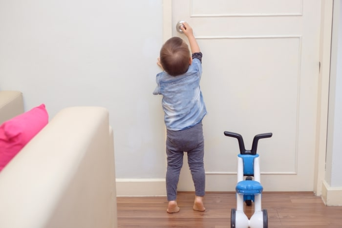 Toddler reaching up to touch door lock.