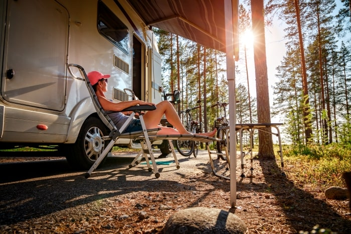 Woman sitting in chair next to RV.