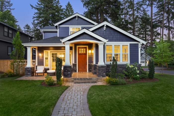Blue Craftsman style home with exterior lights on.