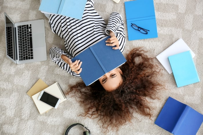 College student laying on bed with notebooks and computer.