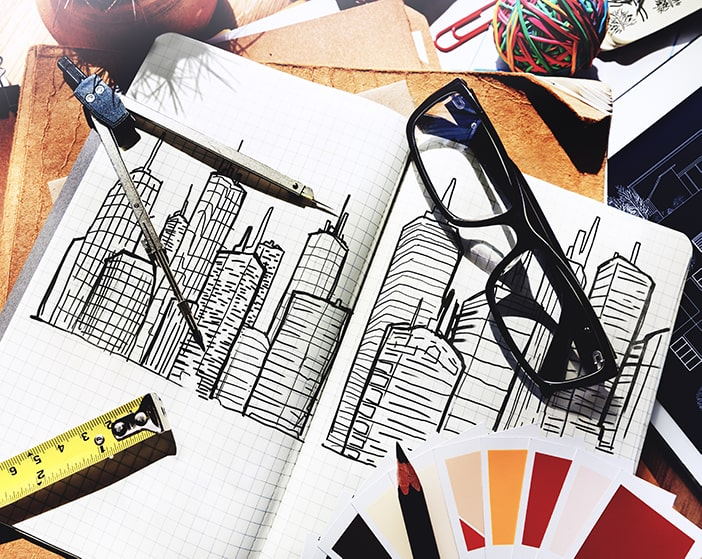 Architect's desk with sketches, glasses and swatches.