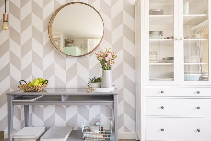 Bright dining room console with geometric wallpaper.