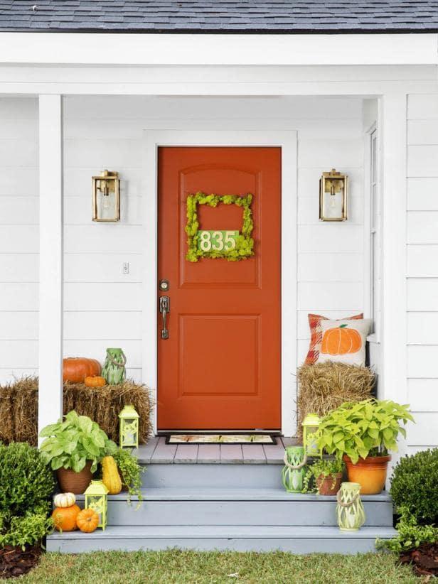 Burnt orange front door with moss wreath.