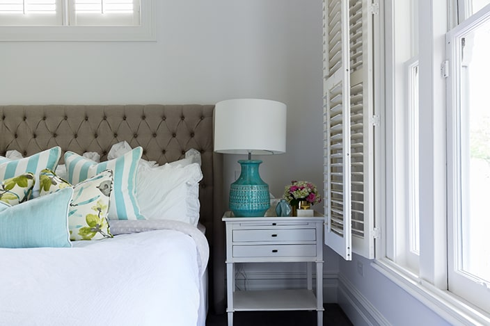 Coastal bedroom with tufted headboard and wooden shutters.