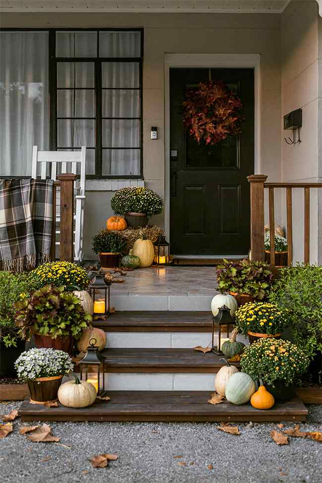 Fall porch with blankets, pumpkins and mums.