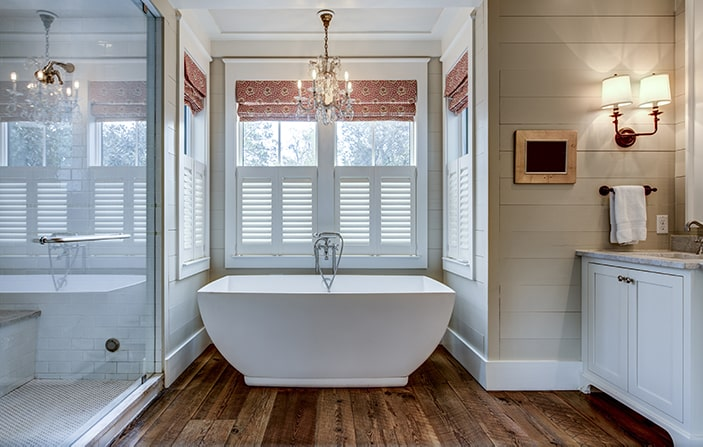 Farmhouse chic bathroom with freestanding bathtub and chandelier.