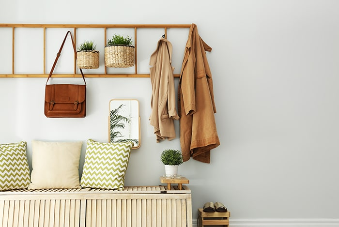 Minimalist entryway with bench and wall hooks.