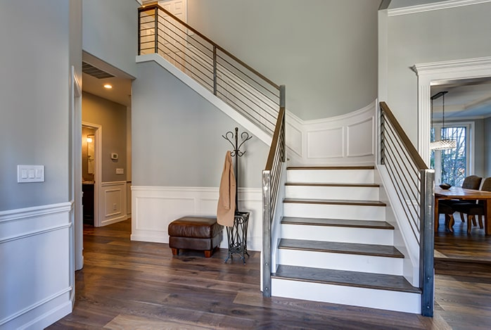 Entryway with wooden stairway and modern railing.