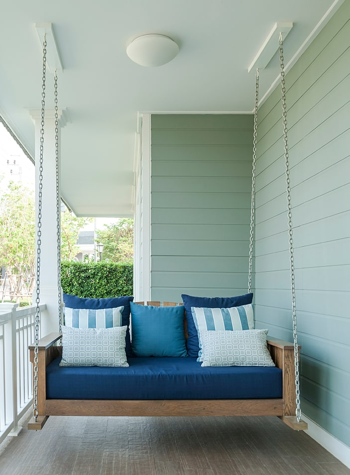 Porch swing with blue cushions.
