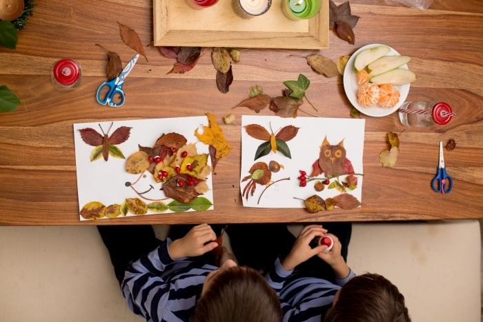 Two kids making fall crafts from leaves.