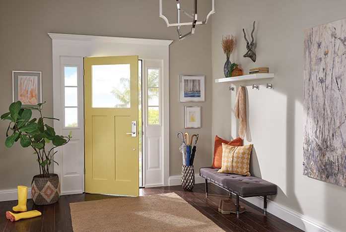 Foyer with yellow front door and Schlage Custom handleset in Bright Chrome.