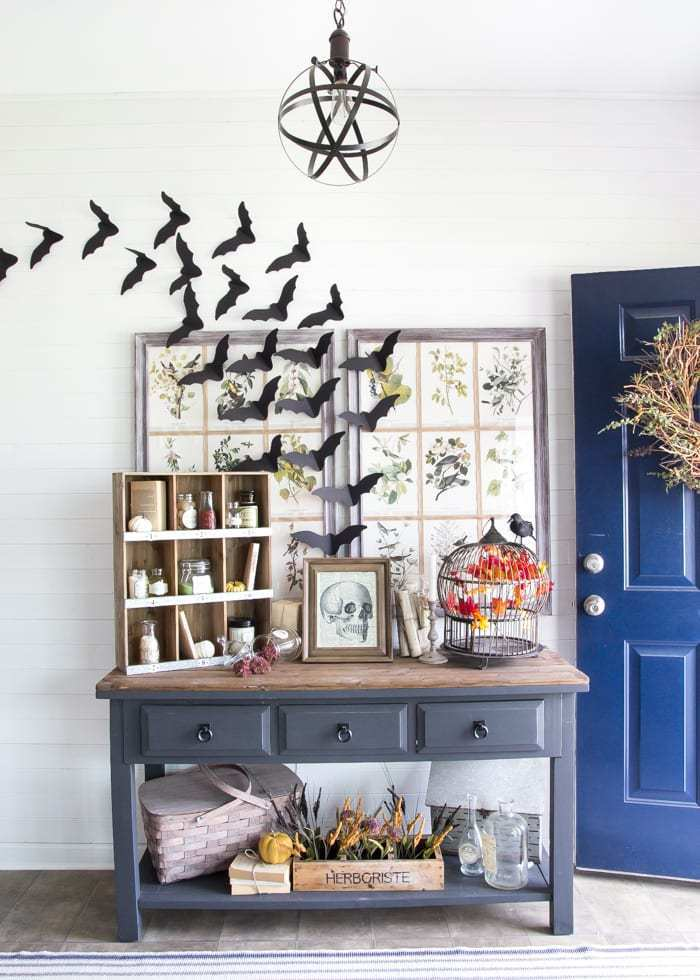 Halloween entryway decor with bats and potions.