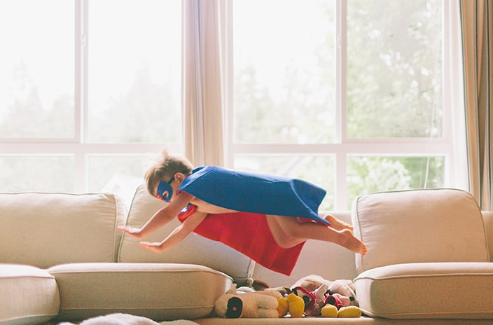 Boy with superhero cape flying over stuffed animals on couch.