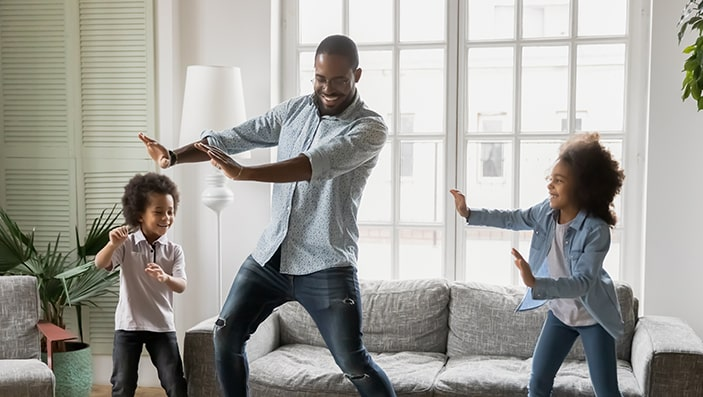 Dad dancing in living room with his two kids.