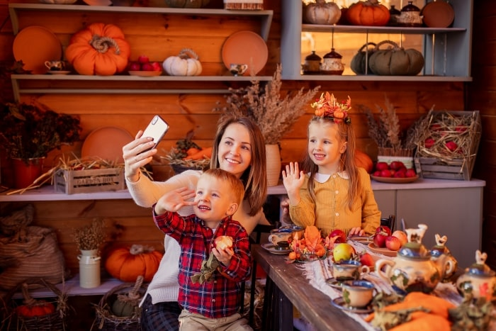 Mom with two children holding up phone to FaceTime family at Thanksgiving table.