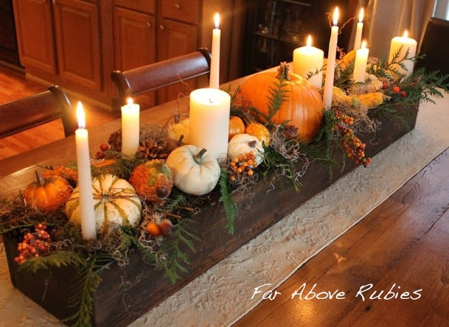 Thanksgiving centerpiece with pumpkins and candles.