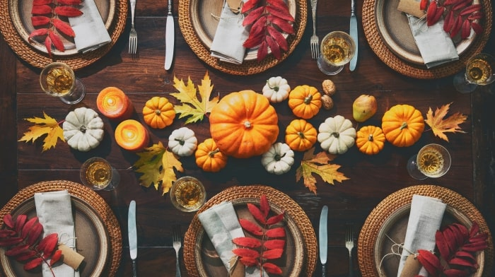 Thanksgiving table with pumpkins as centerpiece.