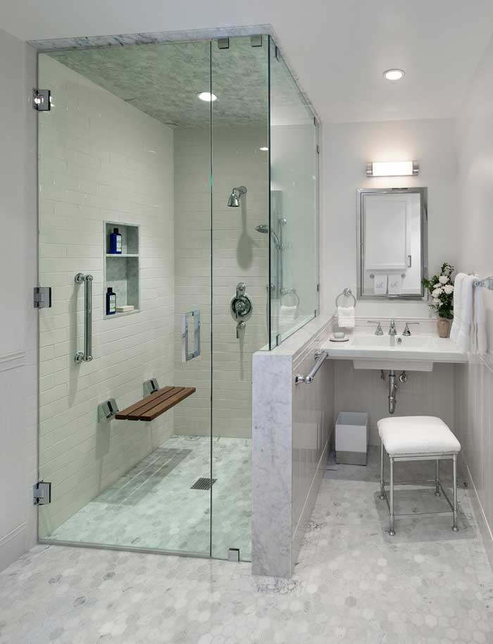 Accessible bathroom with mosaic tile, bamboo shower seat and stylish vanity seating.