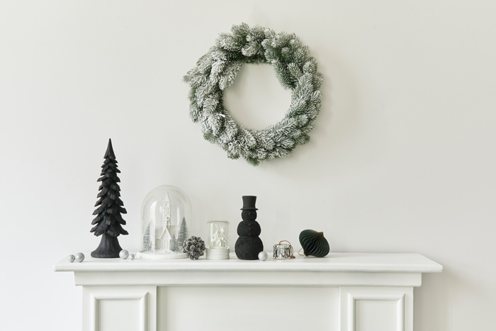 Black and white holiday mantel with black snowman decor.