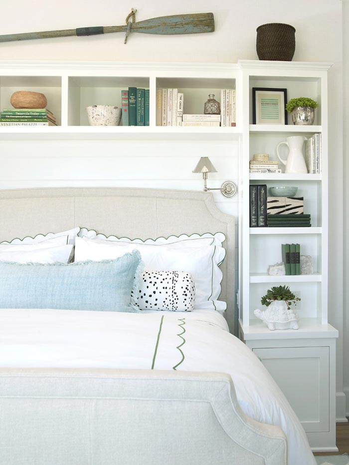 Coastal style bedroom with bookcase surrounding bed.