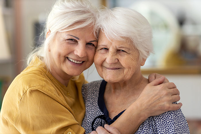 Daughter and elderly mother smiling.