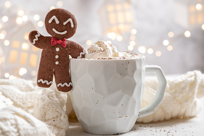 Gingerbread cookie sitting on mug of hot chocolate.