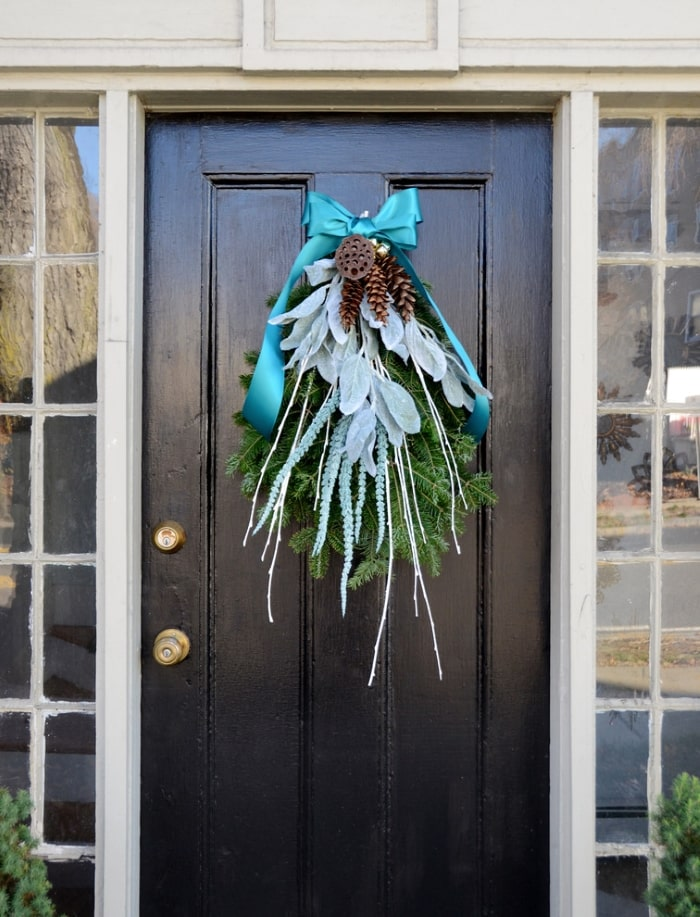 Sprigs of greenery with blue, white and silver accents on front door.