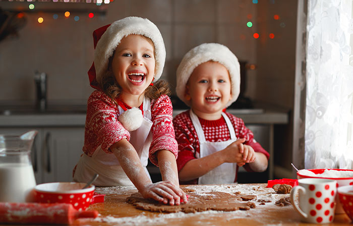 Happy children baking Christmas cookies.