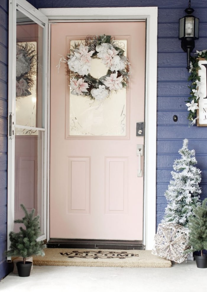 Pale pink front door with white and pink winter wreath.
