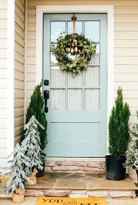 Rainy afternoon front door with natural green Christmas decor.