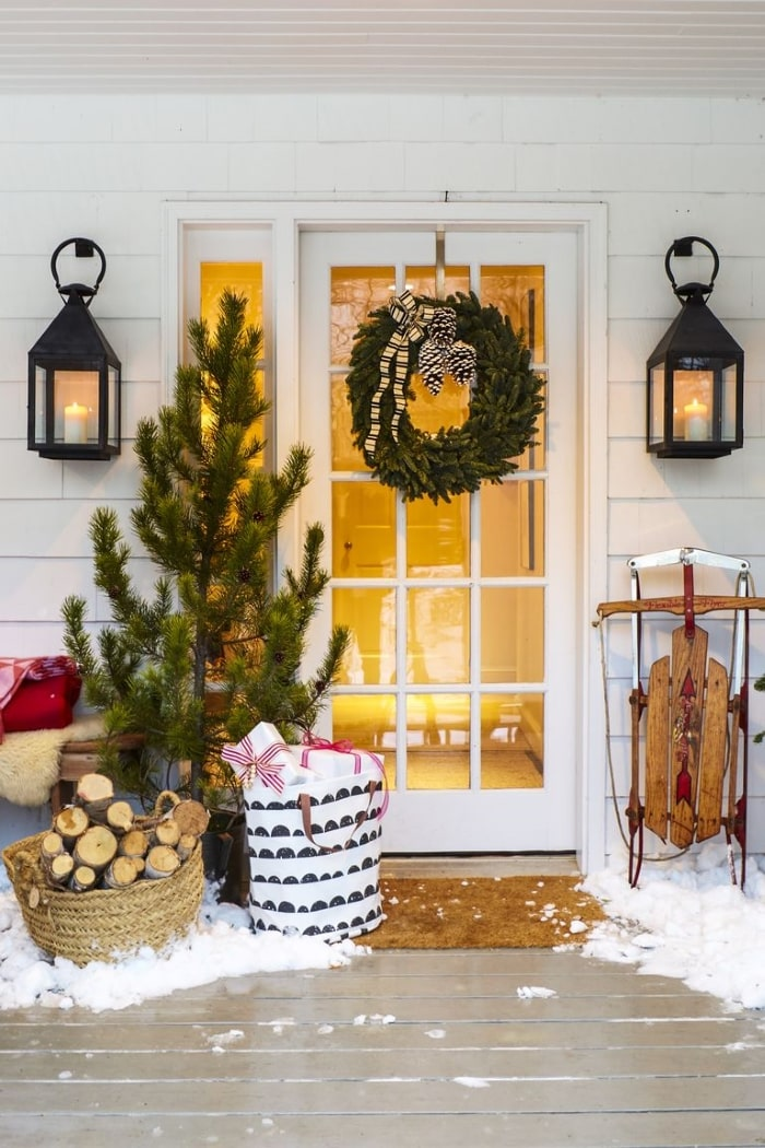 Rustic Christmas front porch with tree and wreath.