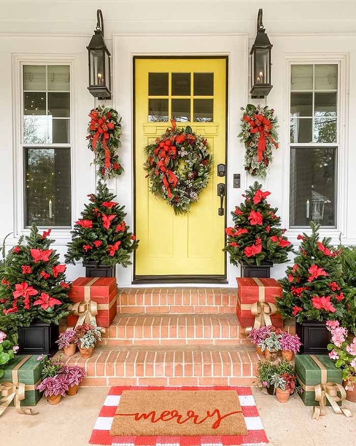 Simply Southern Cottage yellow front door with red Christmas decor.