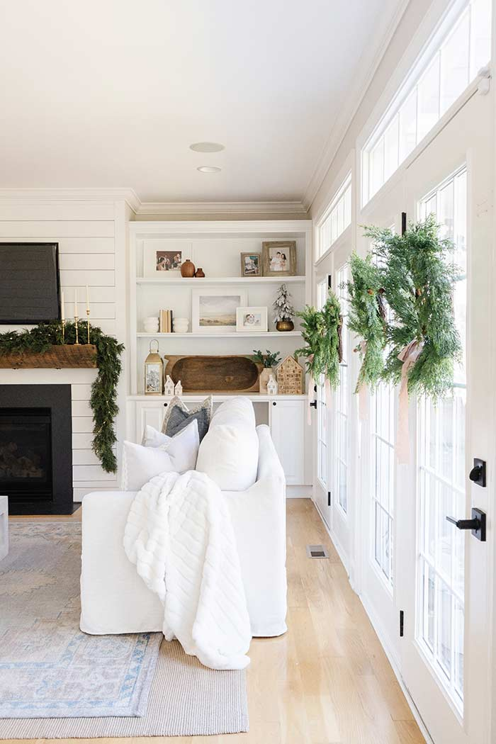 The Coastal Oak living room with indoor wreaths, white couch with blanket.