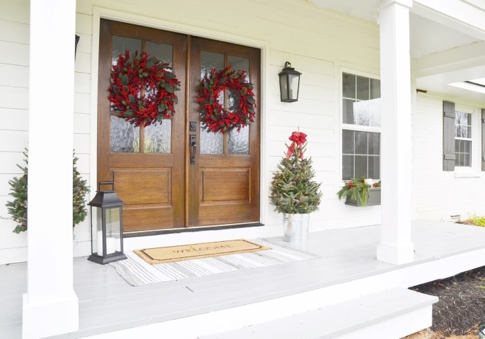 White farmhouse with double entry doors and Christmas wreaths.