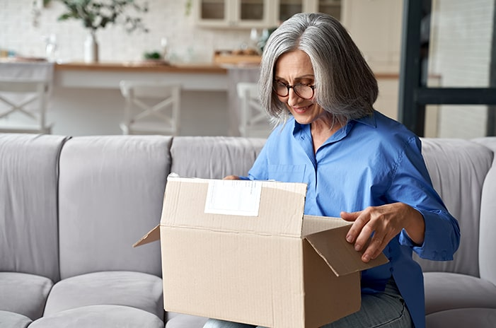 Woman sitting on the couch opening package.