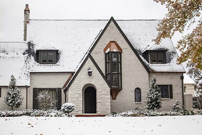 White tudor home with copper accents during winter.