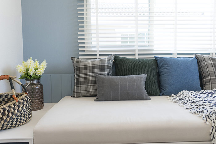 Window seat with blue, grey and green pillows
