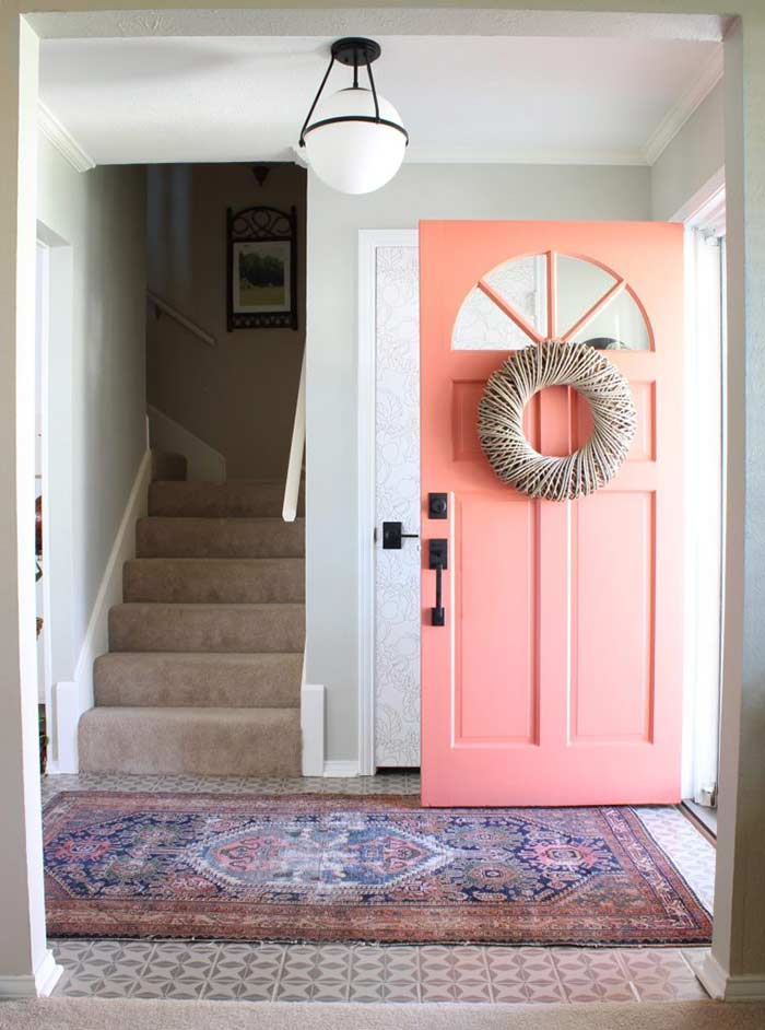 Entryway with coral front door and Matte Black Schlage locks.
