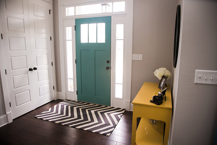 Entryway with chevron rug, yellow table and teal front door.