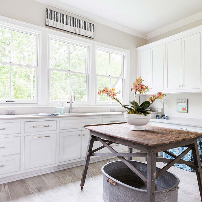 Large white laundry room with reclaimed table and wash tub.