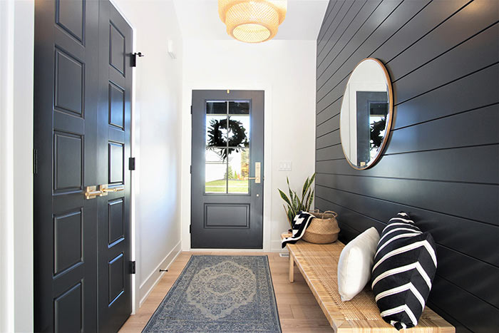 Scandinavian entryway with black shiplap wall.