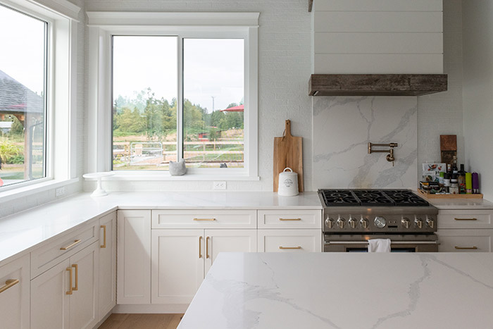 White farmhouse kitchen with brass hardware.
