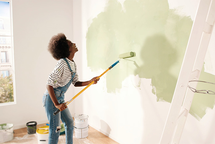 Woman painting wall green.