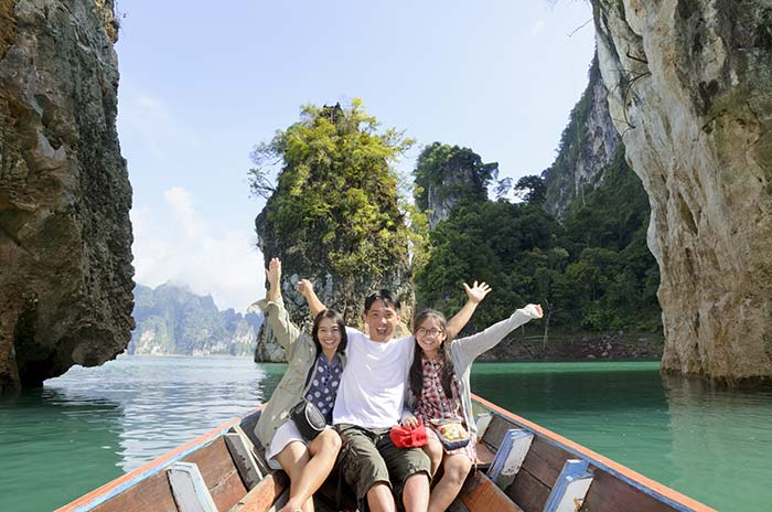 Happy family on vacation in boat on lake.