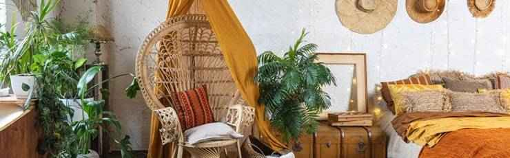Bohemian bedroom with wicker chair, plants and hats on wall.