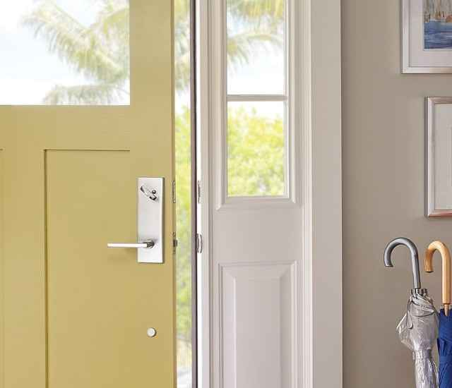 Schlage latitude lever in Bright Chrome on yellow front door.