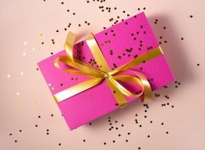 Pink gift box wrapped with gold bow.