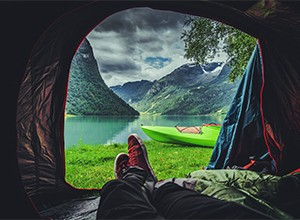 Person laying in tent enjoying view of mountains and water.